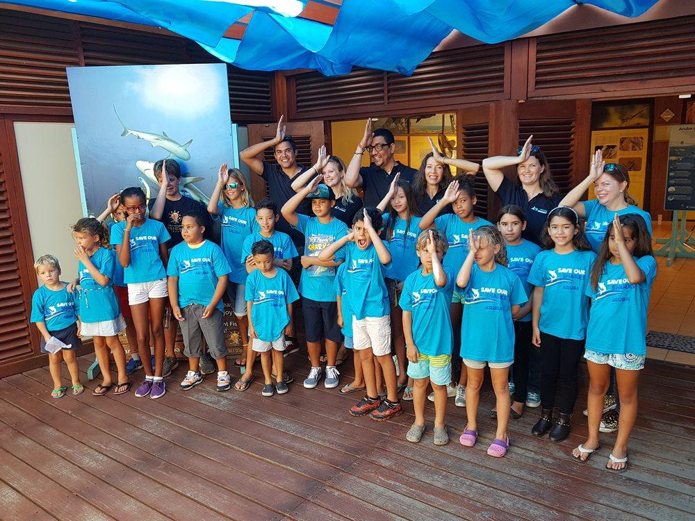 Jörgen Raymann maakt met kinderen het haaiensymbool tijdens een bezoek aan Arikok National Park Aruba.
