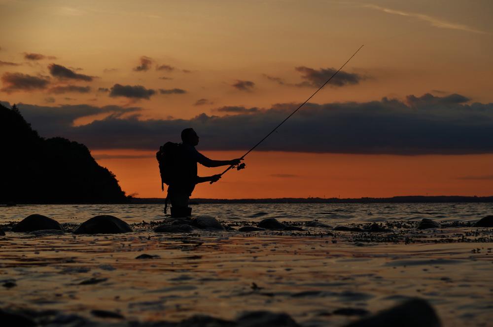 Jagen op zeeforel bij zonsondergang.
