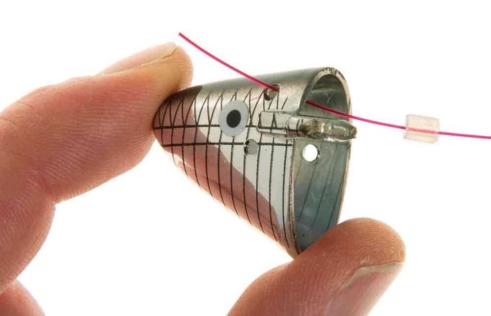 De 'Baitholder' op de onderlijn schuiven, hiervoor het bovenste oog gebruiken. Niet vergeten om de kleine, meegeleverde rubber slang eveneens op de onderlijn te schuiven.