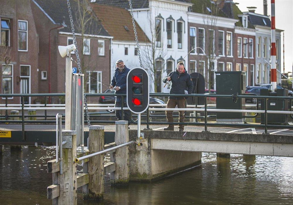 Coen Hansen en Marco Kraal vissend vanaf brug.