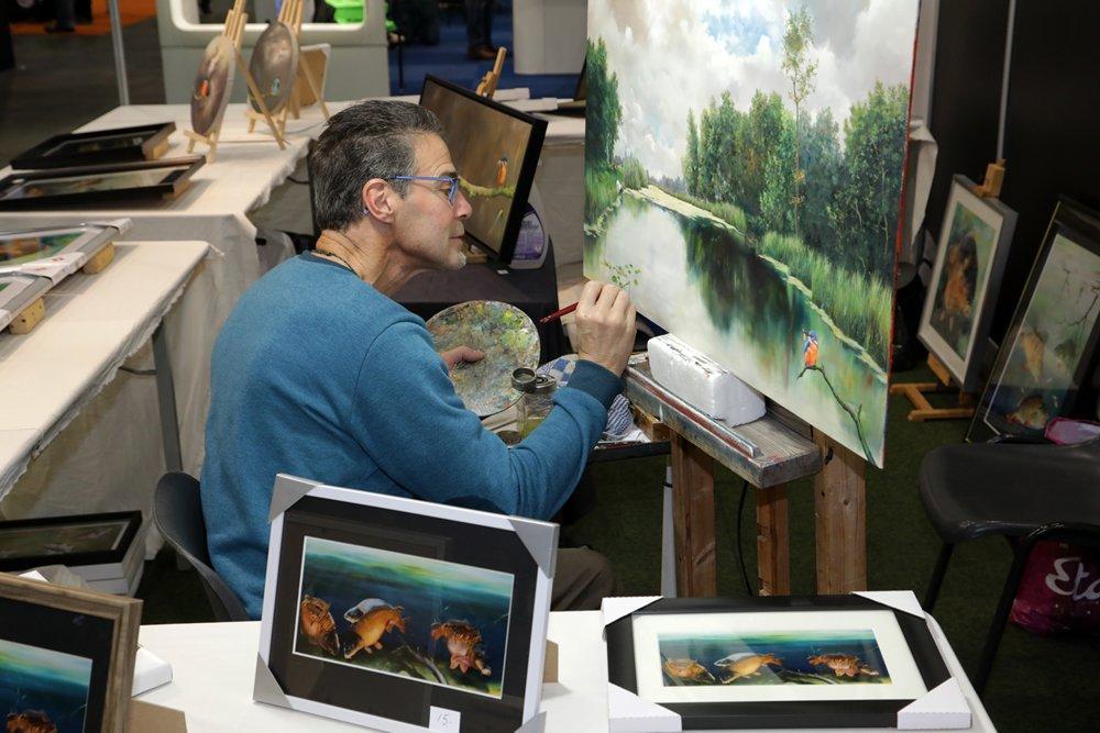 Remko van den Berg aan het werk aan een schilderachtig tafereel.